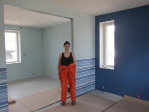 Laura ja Pertti Kröger ovat käteviä käsistään ja tekevät paljon sisustustöitä itse. Tässä Laura poikien huoneiden välisessä isossa oviaukossa. Värejä tässä kodissa käytetään reilusti.