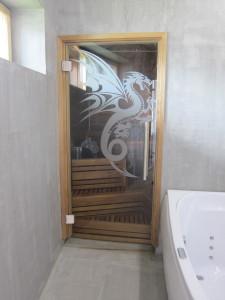 Komea lohikäärme toivottaa tervetulleeksi saunaan (art4u). Interbauen La Spa -amme on upea vastakohta mikrosementtisille seinille ja -lattialle (Decos).