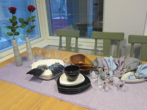 Kauniit yksityiskohdat ovat messutaloissa usein kuvauksen kohteina.  Ruokapöytä ja tuolit ovat ainoat kalusteet, jotka perhe on tuonut uuteen kotiinsa. Kattaus on ikään kuin alkamassa, astiat Amforan, lasit Iittalan, tekstiilit Lapuan Kankurit, puukulho ja serviettirenkaat Werannas