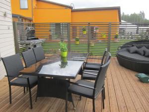 Katetun terassin vieressä avautuu iso kattamaton terassi, jossa on paikka isolle ruokapöydälle ja muhkealle aurinkosohvalle.