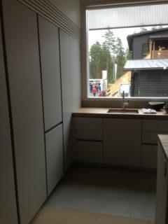 Tässä keittiössä korkeat kaapit on upotettu seinään, kylmälaitteet on integroitu ovien taakse, vetimettömät ovet tekevät seinästä tyylikkään. Talo Koskela, 34.